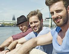 Germany, Cologne, Young men sitting on riverbank - stock photo