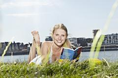Germany, Cologne, Young woman reading book, smiling, portrait Stock Photos