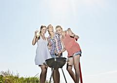 Germany, Cologne, Young women gathered around sausage and drinking beer Stock Photos