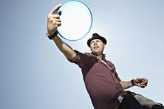 Germany, Cologne, Mature man playing flying disc Stock Photos