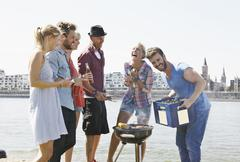 Stock Photo of Germany, Cologne, Group of people gathered around barbecue