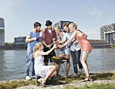 Germany, Cologne, Group of people gathered around barbecue - stock photo