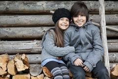Germany, Huglfing, Girl and boy sitting on stack of firewood, smiling, portrait Stock Photos