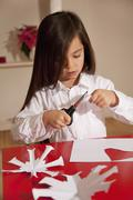 Girl cutting snowflake shape for christmas decoration Stock Photos