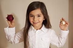 Girl holding christmas bauble, smiling, portrait - stock photo
