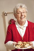 Senior woman with christmas cookies, smiling, portrait Stock Photos