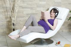 Germany, North Rhine Westphalia, Pregnant woman reading book and listening music Stock Photos