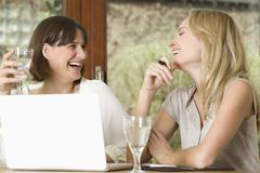 Stock Photo of Germany, North Rhine Westphalia, Women sitting at table with laptop, smiling