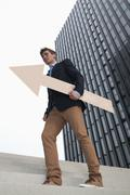 Germany, North Rhine Westphalia, Duesseldorf, Young businessman walking on steps - stock photo