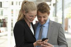 Germany, North Rhine Westphalia, Duesseldorf, Business people using smart phone Stock Photos