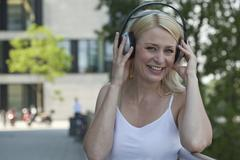 Germany, North-Rhine-Westphalica, Duesseldorf, Mid adult woman with headphone, Stock Photos