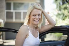 Germany, North-Rhine-Westphalica, Duesseldorf, Mid adult woman leaning on car, Stock Photos