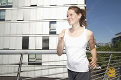 Germany, North-Rhine-westphalia, Duesseldorf, Young woman running, smiling Stock Photos
