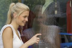 Germany, North Rhine Westphalia, Cologne, Young woman at window shopping - stock photo