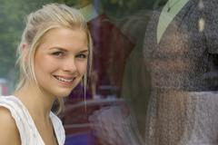 Germany, North Rhine Westphalia, Cologne, Young woman at window shopping, - stock photo