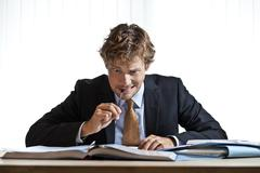 perplexed businessman working on problem - stock photo