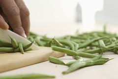 Mid adult man cutting string beans on wooden board with ceramic knife - stock photo