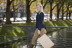 Europe, Germany, North Rhine Westphalia, Duesseldorf, Young woman walking with - stock photo