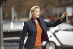 Europe, Germany, North Rhine Westphalia, Duesseldorf, Young woman hailing taxi - stock photo