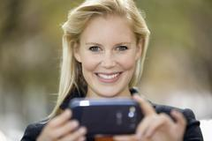 Stock Photo of Europe, Germany, North Rhine Westphalia, Duesseldorf, Young woman using smart
