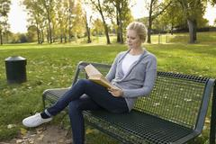Stock Photo of Europe, Germany, North Rhine Westphalia, Duesseldorf, Young woman reading book
