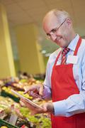 Stock Photo of Germany, Cologne, Mature man using digital tablet in supermarket