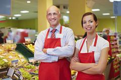 Germany, Cologne, Man and woman standing in supermarket, smiling, portrait - stock photo