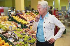 Germany, Cologne, Mature woman thinking in supermarket - stock photo