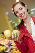 Germany, Cologne, Young woman comparing apples in supermarket Stock Photos