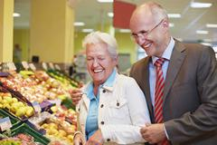 Stock Photo of Germany, Cologne, Mature couple in supermarket, smiling