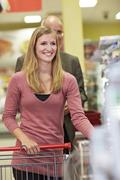 Germany, Cologne, Man and woman waiting in supermarket, smiling - stock photo