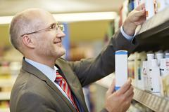 Stock Photo of Germany, Cologne, Mature man in supermarket, smiling