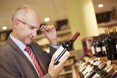Germany, Cologne, Mature man inspecting wine bottle in supermarket - stock photo