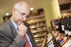Germany, Cologne, Mature man inspecting wine in supermarket Stock Photos