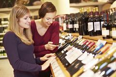 Germany, Cologne, Young women inspecting wine in supermarket Stock Photos