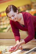 Stock Photo of Germany, Cologne, Young woman with raspberries in supermarket
