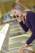 Germany, Cologne, Young woman standing at freezer in supermarket - stock photo