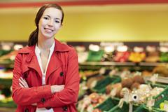 Germany, Cologne, Young woman in supermarket, smiling, portrait - stock photo