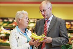 Stock Photo of Germany, Cologne, Mature couple with bananas in supermarket