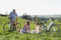 Germany, Bavaria, Senior man and mature women talking on hill with electric Stock Photos