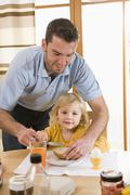 Father spreading butter on bread for daughter breakfast - stock photo