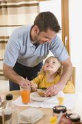 Father spreading butter on bread for daughter breakfast Stock Photos