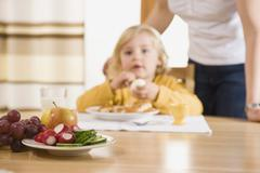 Fresh fruits on table, girl having breakfast in background Stock Photos