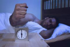Man turning off alarm clock with fist Stock Photos