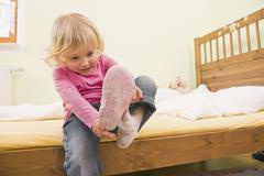 Stock Photo of Girl sitting on bed and putting shoes