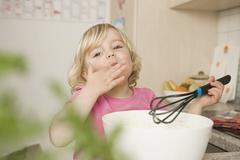 Girl preparing cake, tasting batter Stock Photos
