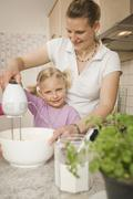Mother and daughter mixing batter with electric whisk Stock Photos