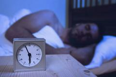 Alarm clock on table, man sleeping in background Stock Photos
