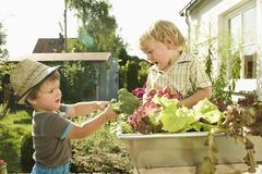 Stock Photo of Germany, Bavaria, Boys holding broccoli