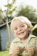 Germany, Bavaria, Boy holding red currants, smiling, portrait Stock Photos